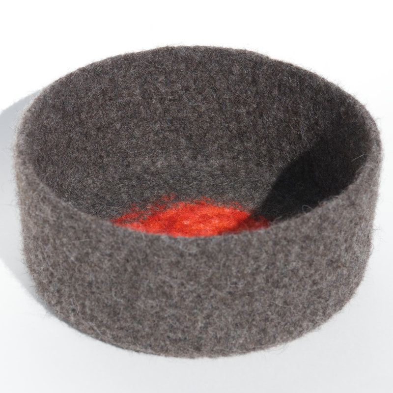 ORB is a large hand-felted bowl in gunmetal color with zinnia circle inset on the bottom